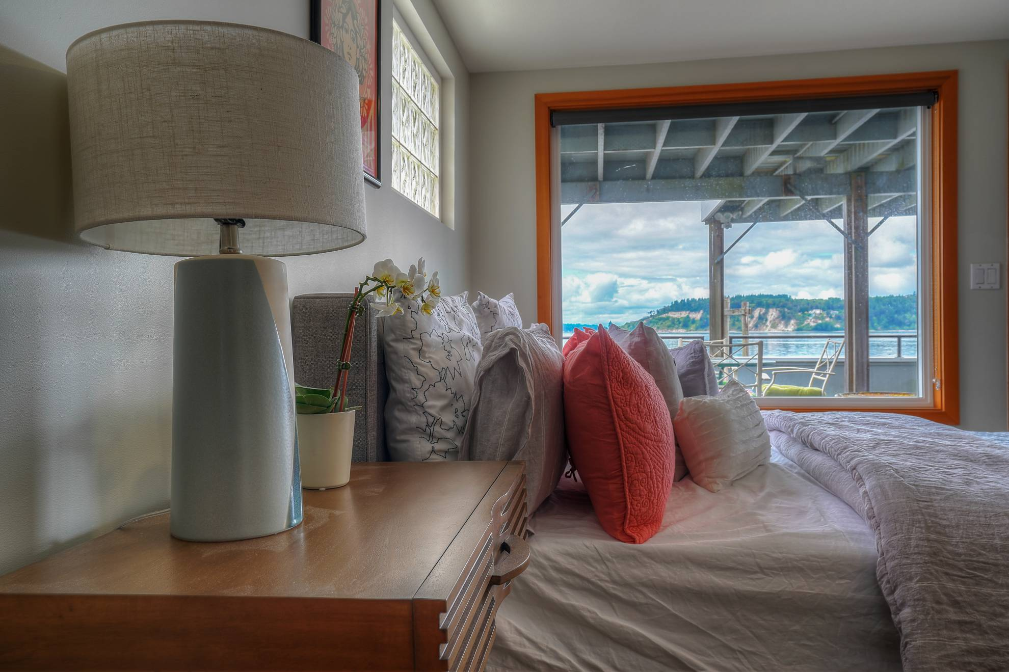 Master bedroom with large window and porch overlooking the water